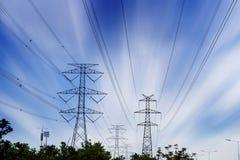 Gesilhouetteerde elektriciteitspylonen, machtslijnen en bomen Stock Foto's