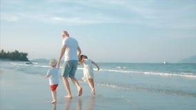 Gesilhouetteerde gelukkige Vader en Dochter en Zoon die en pret op het strand spelen hebben bij zonsondergang Langzame Motie Gelu stock video