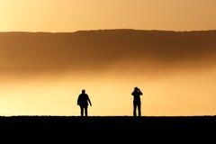 Gesilhouetteerde mensen bij de zonsondergang Royalty-vrije Stock Foto's
