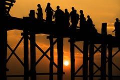 Gesilhouetteerde mensen die de brug van U bein met zonsondergang kruisen Royalty-vrije Stock Foto's
