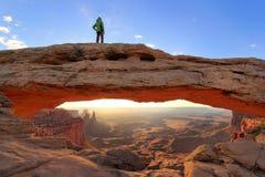Gesilhouetteerde persoon die zich bovenop Mesa Arch, Nationaal Canyonlands bevinden Stock Foto