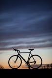 Gesilhouetteerde rasfiets in zonsondergang Stock Afbeeldingen