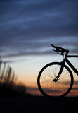 Gesilhouetteerde rasfiets in zonsondergang Royalty-vrije Stock Foto