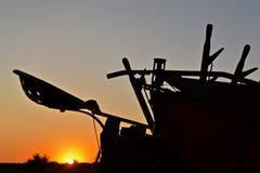 Gesilhouetteerde verlaters en zetel van een oude de landbouwmachine royalty-vrije stock foto's