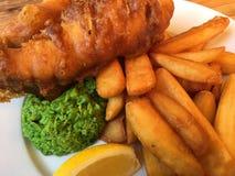 Geslagen vis met patat, met zachte erwten stock afbeelding