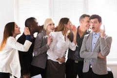 Gesloten bedrijfscollega's die in het bureau fluisteren stock afbeeldingen