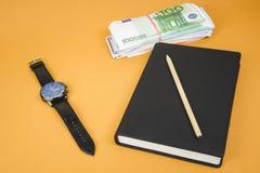 gesloten blocnote, klok, contant geld en potlood die op het op bureau oranje lijst leggen stock afbeelding
