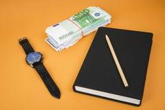 gesloten blocnote, klok, contant geld en potlood die op het op bureau oranje lijst leggen stock foto's