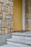 Gesloten gele verticale roldeur en steenbakstenen gekleurde muur Royalty-vrije Stock Foto's