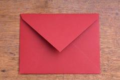 Gesloten geweeste Rode Envelop op een Houten Lijst Stock Afbeelding