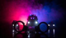 Gesloten handcuffs op de straatbestrating bij nacht met politiewagenlichten stock foto