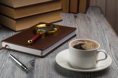 Gesloten notitieboekje met een vulpen op rustieke lijst Vergrootglas op een blocnote Stock Fotografie