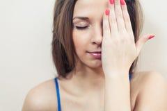 Gesloten ogenvrouwen die haar oog met de hand verbergen Stock Foto