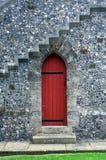 Gesloten rode deur onder steentreden op steenmuur stock fotografie