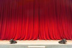Gesloten rode gordijn achtergrond verlichte schijnwerperstraal Theatraal Gordijn stock foto