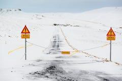 Gesloten weg met aandachtstekens, onoverschrijdbaare grintweg in de winter, IJsland stock foto