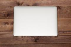 Gesloten zilveren laptop op bruine houten lijst Royalty-vrije Stock Foto