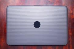 Gesloten zwarte laptop ligt op lijst van rood hout Stock Afbeelding