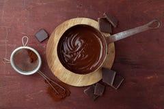 Gesmolten chocoladewerveling in pan op de houten achtergrond Stock Afbeeldingen