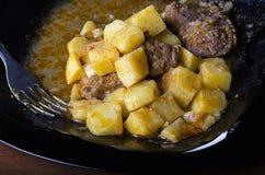 Gesmoorde aardappels met vlees en jus op een zwarte plaat, close-up 45 mening royalty-vrije stock foto's