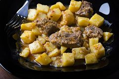 Gesmoorde aardappels met vlees en jus op een zwarte plaat, close-up 45 mening stock foto's