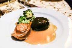 Gesmoorde abalone met paddestoel en broccoli in superieure saus stock foto