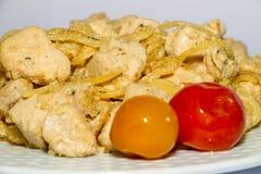 Gesmoorde kippenborst met gekookte macaroni en rode en gele tomaten op een witte achtergrond stock afbeeldingen