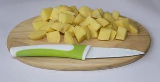 Gesneden aardappels op een scherpe raad met een mes Stock Afbeelding