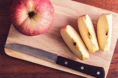 Gesneden appel en mes op houten lijst Stock Afbeelding