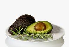 Gesneden avocado en een twijg van rozemarijn op een plaat Royalty-vrije Stock Afbeelding
