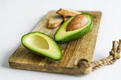 Gesneden avocado op houten scherpe Raad stock afbeeldingen