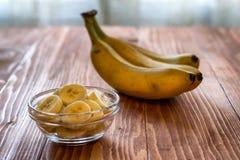 Gesneden banaan in kom op houten lijst Stock Afbeeldingen