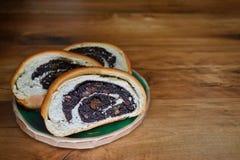 Gesneden blozend vers brood met papaverzaden die op een ronde kleiplaat liggen op een houten oppervlakte met copyspace stock afbeelding