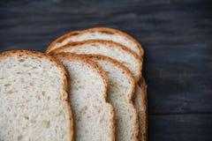 Gesneden brood dicht omhoog hoogste mening - Geheel die tarwebrood op houten dark wordt gesneden royalty-vrije stock afbeelding