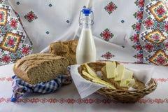 Gesneden brood en boter in een rieten mand en een flessenmelk Royalty-vrije Stock Afbeeldingen