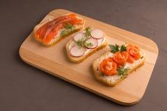 Gesneden brood met zalmplakken, kersentomaten stock afbeeldingen