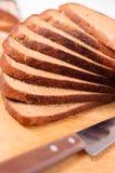 Gesneden brood op een houten scherp raad en een mes Stock Afbeeldingen