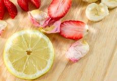 Gesneden citroen, aardbeien, banaan en roze-bloemblaadjes op houten raad Stock Foto's