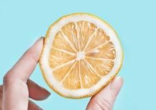 Gesneden citroen met vingers die het drukken Stock Fotografie