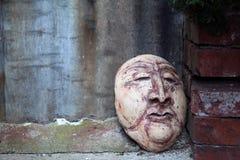 Gesneden Clay Face Leaning Against een Rode Bakstenen muur stock foto