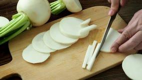 Gesneden daikon radijs Smakelijke verse ruwe witte ronde Japanse radijs met groene stammen en bladeren stock video