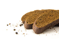 Gesneden die brood met zwarte peper op wit wordt geïsoleerd Stock Foto's
