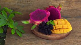 Gesneden draakfruit en mango op een oude houten achtergrond stock videobeelden