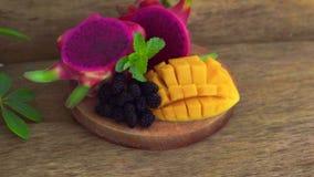 Gesneden draakfruit en mango op een oude houten achtergrond stock video