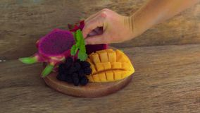 Gesneden draakfruit en mango op een oude houten achtergrond stock footage