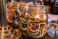 Gesneden droge sinaasappel in de glaskruik als ingrediënt voor dranken stock afbeelding