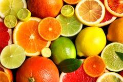 Gesneden en gehele citrusvruchten met bladeren als achtergrond royalty-vrije stock foto's