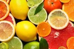 Gesneden en gehele citrusvruchten met bladeren als achtergrond stock foto