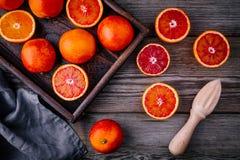 Gesneden en gehele rijpe sappige bloedsinaasappelen en grapefruit in de doos op houten achtergrond stock fotografie