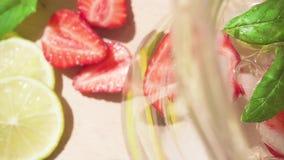 Gesneden fruit in een zachte nadruk en een karaf met een gekoelde drank stock footage